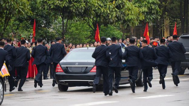 Bodyguards running next to a limousine