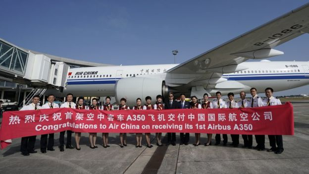 Air China staff standing in front of a new Airbus plane