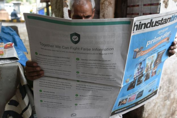 An Indian newspaper vendor reads a newspaper with a full back page advertisement from WhatsApp intended to counter fake information in Delhi on July 10 2018.