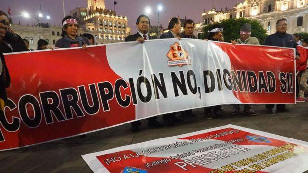 """Manifestantes con una pancarta que dice """"corrupción no, dignidad sí""""."""