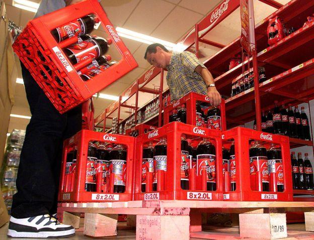 Empleados en Bélgica retiran botellas de Coca-Cola de un supermercado, en junio de 1999.