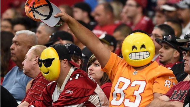 Hombre lleva máscara de un emoji en un partido de beisbol