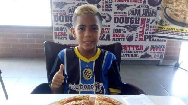 Brayan Navarro comiendo pizza luego de un partido de futbol