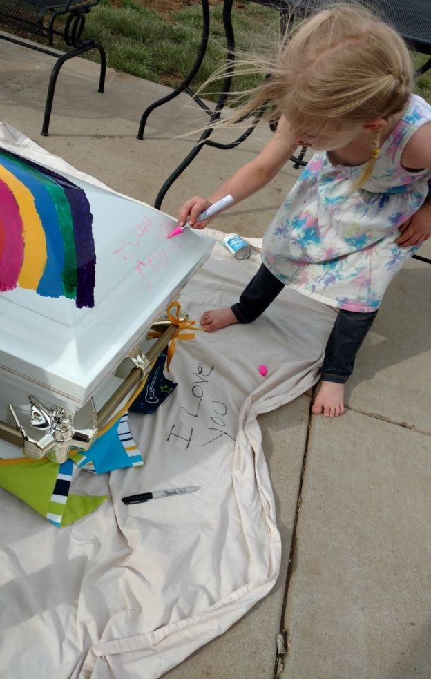criança escreve em caixão de outra criança