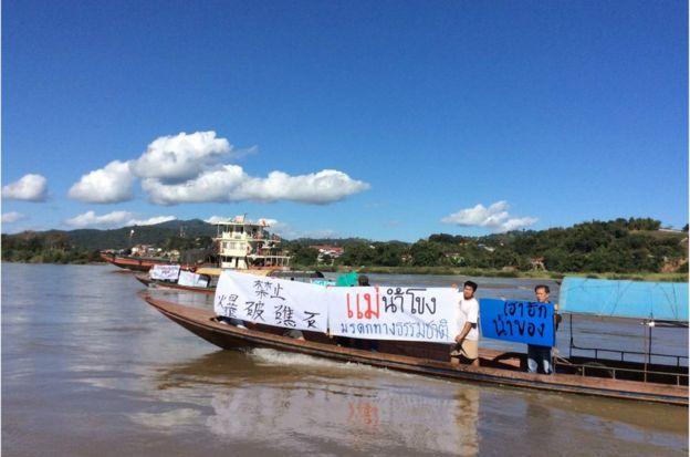 """當地漁民手持""""禁止爆破礁石""""等中泰文的示威標語,反對在湄公河沿岸爆破礁石。"""