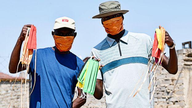 Hombres sosteniendo mascarillas en el municipio de Nkowankowa, Sudáfrica.