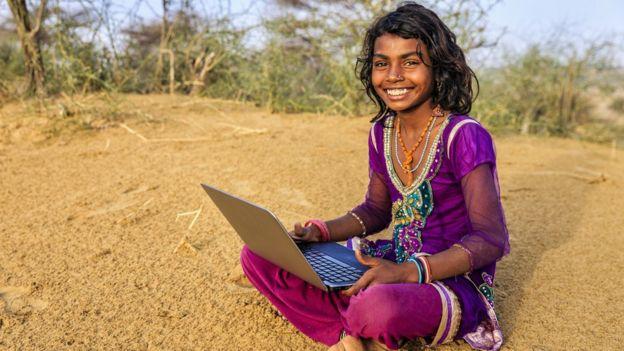 Niña en región rural de India con una computadora portátil