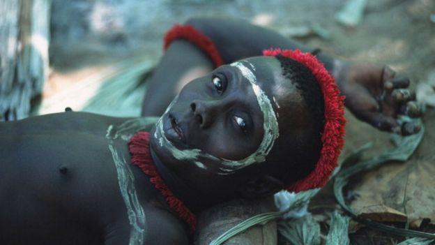 Um jawara olha para a câmera com o rosto pintado
