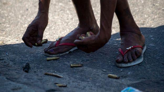 Una persona junta cartuchos de bala en una favela de Rio de Janeiro.