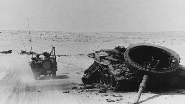 An Israeli tank driving past a destroyed tank in October 1973