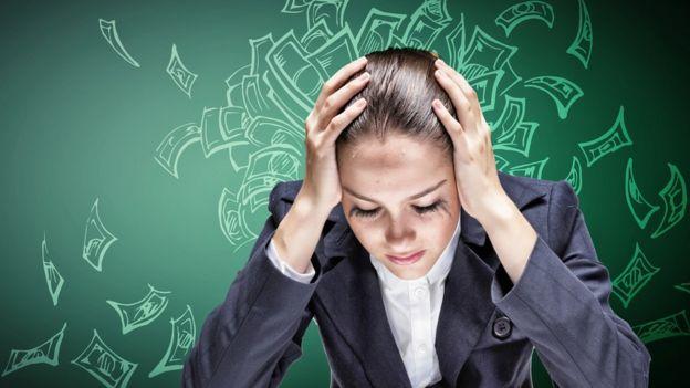 Mujer joven con manos en la cabeza preocupada por dinero.