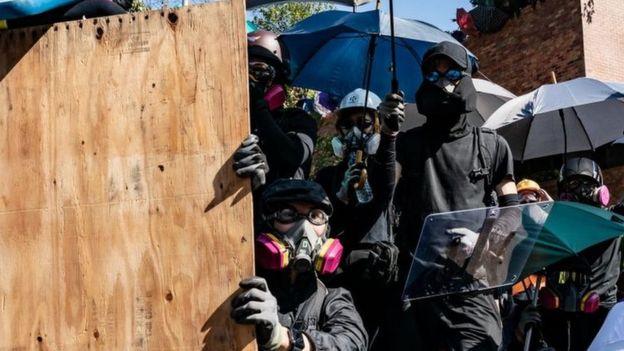 Демонстранты в очках и масках, со щитами и зонтиками