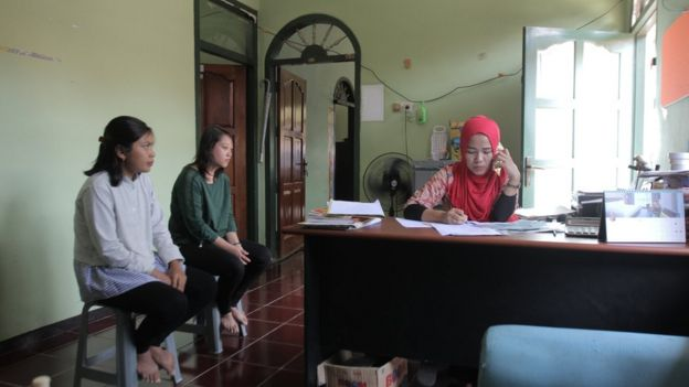 Dua calon pekerja domestik menunggu manajer pelatihan.