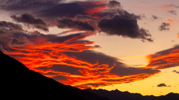 Nuvens vermelhas e laranjas sobre montanhas escuras