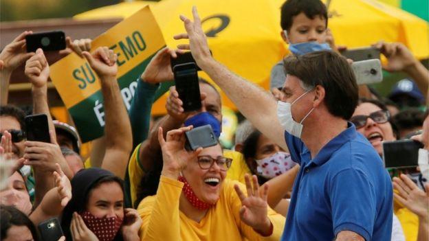 Bolsonaro, de máscara, acena para apoiadores em Brasília