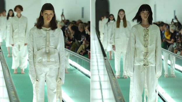 Two models wearing the 'straitjacket' jumpsuits on the catwalk