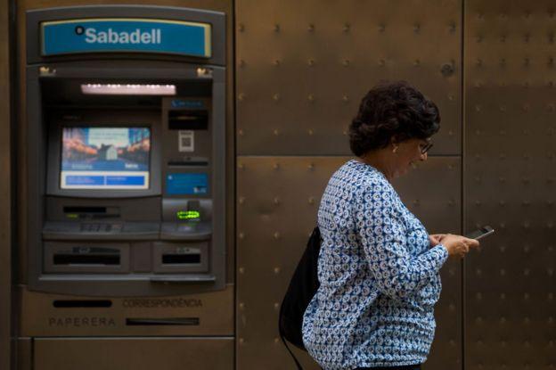 Mujer frente a un cajero del Banco Sabadell en Barcelona.