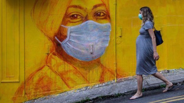 香港街头戴口罩的路人与壁画相呼应