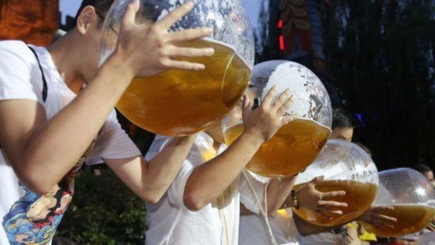Jovens bebendo cerveja em grandes recipientes