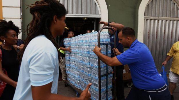 Homem empurra carrinho com garrafas de água.