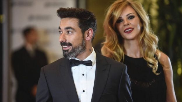 Argentine footballer Ezequiel Lavezzi and his wife pose on a red carpet upon arrival to attend Argentine football star Lionel Messi and Antonella Roccuzzo