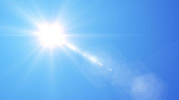 Sol brillando en cielo azul.
