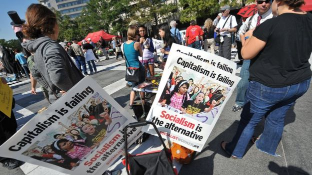 Pessoas protestam segurando cartazes contra o capitalismo