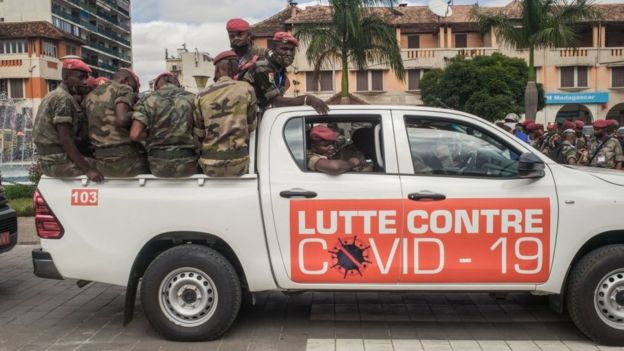 """Soldiers in a pick-up truck with the sign saying """"Lutte Contre Covid-19"""" (Fight against Covid-19) in Antananarivo, Madagascar - April 2020"""