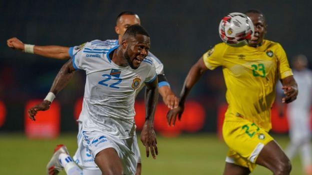 Le Chancel Mangulu Mbemba, de la RD Congo (à gauche), reprend la balle dans les filets du gardien de but zimbabwéen.