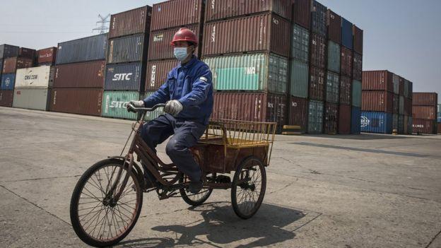 Рабочий на велосипеде в уханьском речном порту