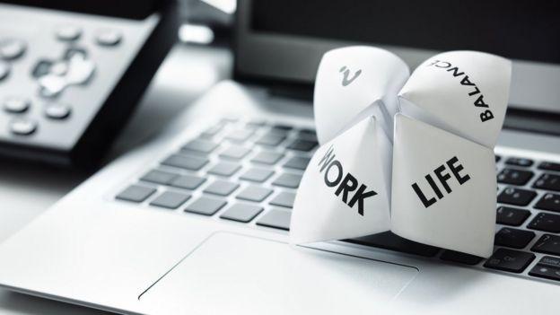"""Papel en el que se lee """"vida"""" y """"trabajo"""" sobre una computadora."""