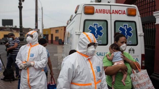 Trabajadores de la salud con equipos de protección personal frente a una ambulancia en Perú