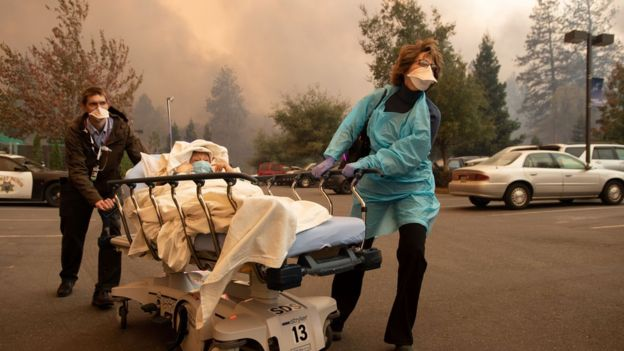 Patients are quickly evacuated from the Feather River Hospital as it burns down during the Camp fire in Paradise