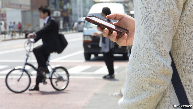 Man using mobile phone on street in Tokyo, Japan