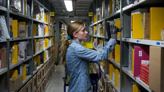Una mujer en un almacén de Amazon.