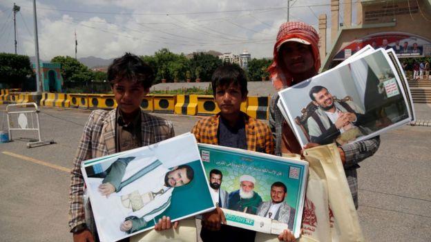 Jóvenes yemeníes con fotografías del líder rebelde hutí