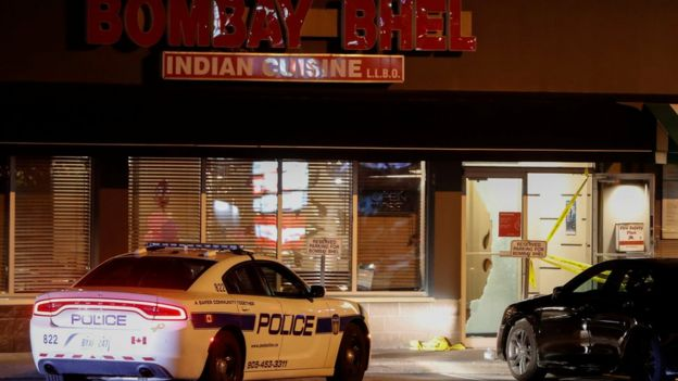 A police car is parked in front of shattered glass at the Bombay Bhel restaurant