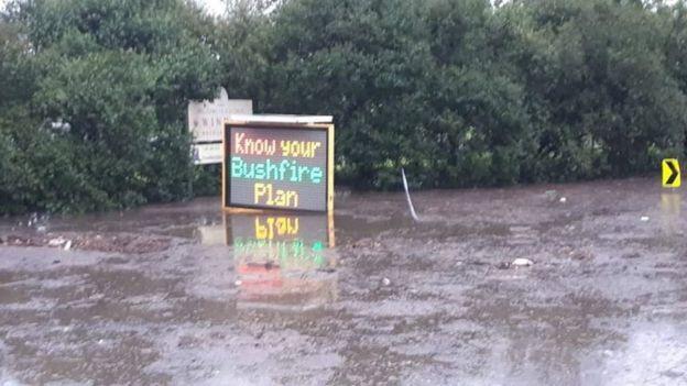 Flood waters lap a bushfire warning road sign