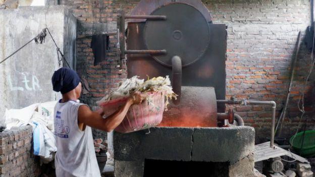 Un hombre coloca un fardo de plástico en un incinerador