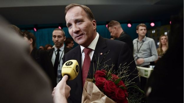 Swedish PM Stefan Löfven talks to the press, carrying red roses, after a TV debate on 7 September 2018