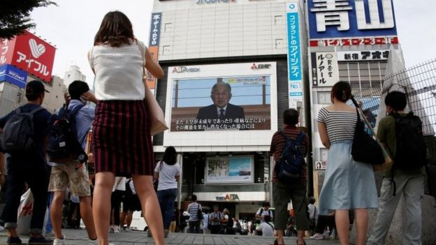People watch a large screen showing Japanese Emperor Akihito's video address in Tokyo, Japan, August 8, 2016