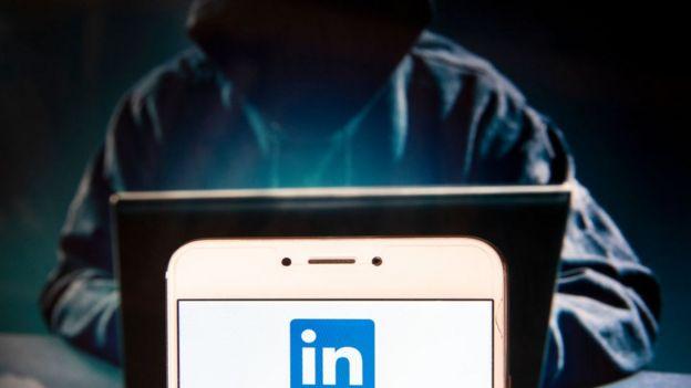 Persona encapuchada mirando una pantalla de una computadora y el logo de LinkedIn