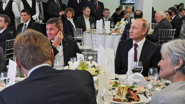 In this file photo taken on 10 December 2015, Russian President Vladimir Putin is seen centre right with retired US Lt Gen Michael Flynn, center left