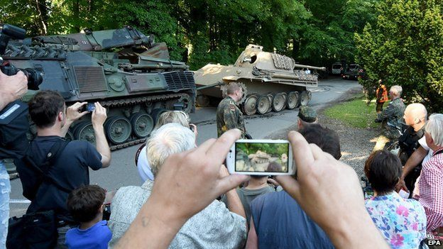 A crowd of people photographing the Panther tank after it was removed