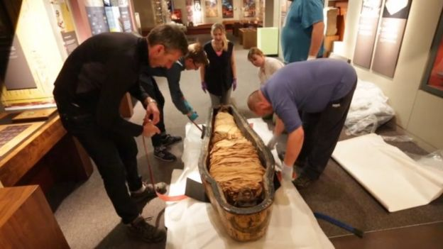 Nesyamun's mummified remains being lifted out of a coffin at Leeds City Museum