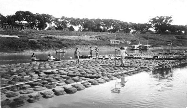 Foto histórica de jangada para transporte de borracha em rio no Acre, com seringueiros sobre boias.