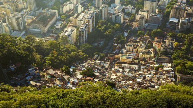 Fotografia aérea de uma favela, em um morro, cercada de prédios