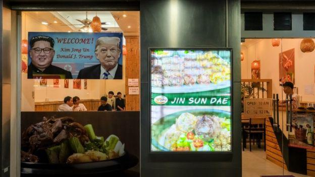 Cartel de bienvenida a Kim y Trump