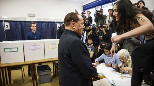 投票所に到着したベルルスコーニ元首相に、フェミニスト活動家が上半身裸で抗議行動をした