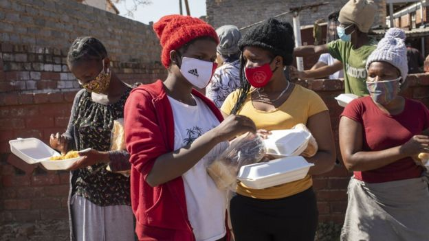 """Women receive bread at a food handout during the Eid al Adha at the """"Hunger Has No Religion"""" feeding scheme, in Johannesburg, South Africa"""